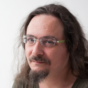 Kit O'Connell, an Austin-based gonzo journalist, has white skin, long brown hair and glasses with a goatee and moustache