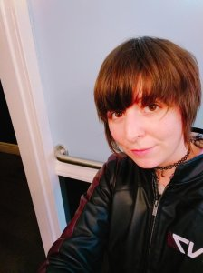 Composer Emily Meo, with short brown hair and bangs, wearing a black zip-up jacket.
