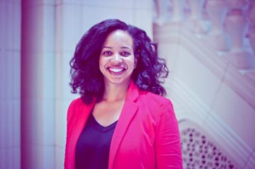 Yamani Hernandez, a woman with dark brown hair and brown skin, smiling and wearing a red blazer.